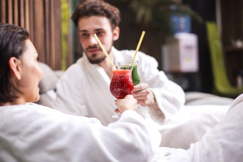 好淫夫妇敬酒与杯汁液 免版税库存图片