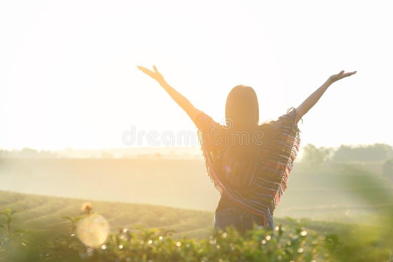 好生活方式旅客妇女愉快的感觉日出早晨放松和面对在自然茶农场的自由, 免版税库存图片