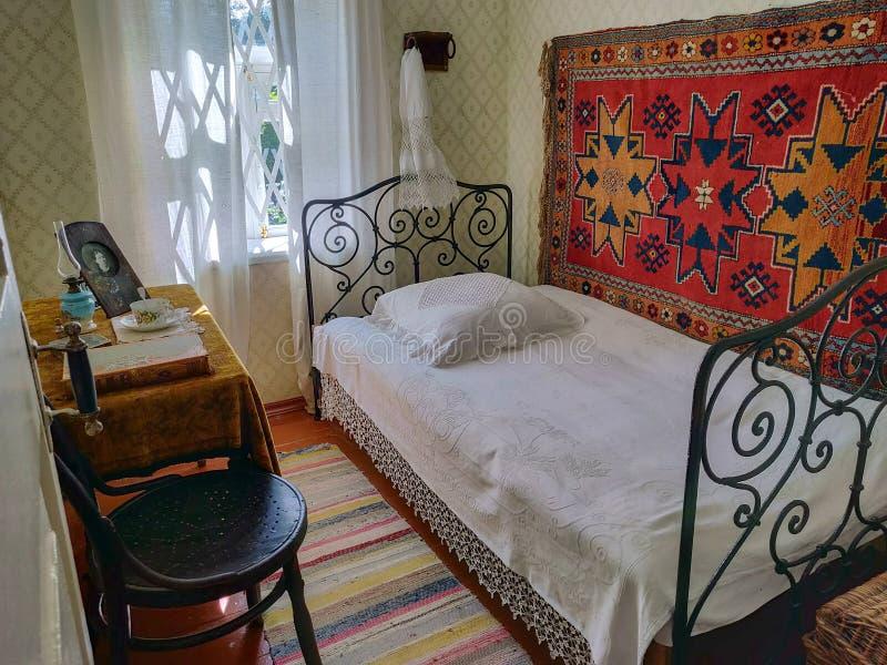 好的卧室内部葡萄酒农村样式的 有舒适的机盖双人床和减速火箭的椅子的室 免版税图库摄影