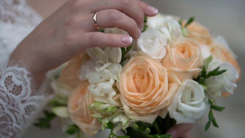 好的婚礼花束在新娘` s手上 夹子 拿着婚礼的美丽的花束一件美丽的白色礼服的未婚妻 库存照片