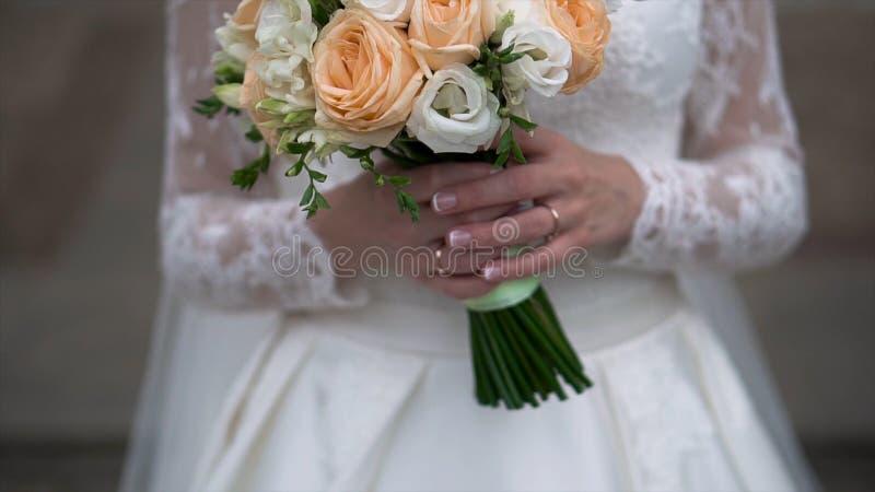 好的婚礼花束在新娘` s手上 夹子 拿着婚礼的美丽的花束一件美丽的白色礼服的未婚妻 库存图片