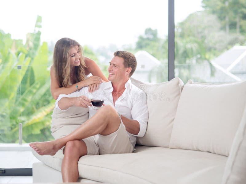 好的年轻夫妇看法坐在summ的沙发 库存图片