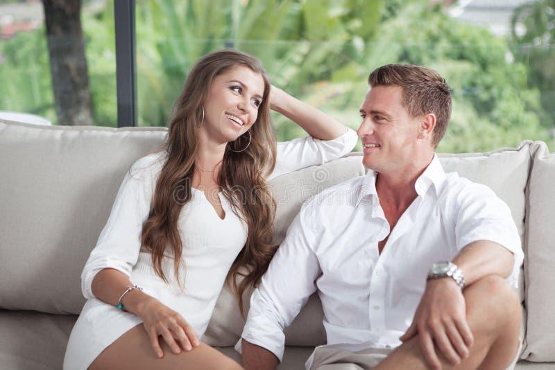 好的年轻夫妇看法坐沙发在避暑别墅里 库存图片