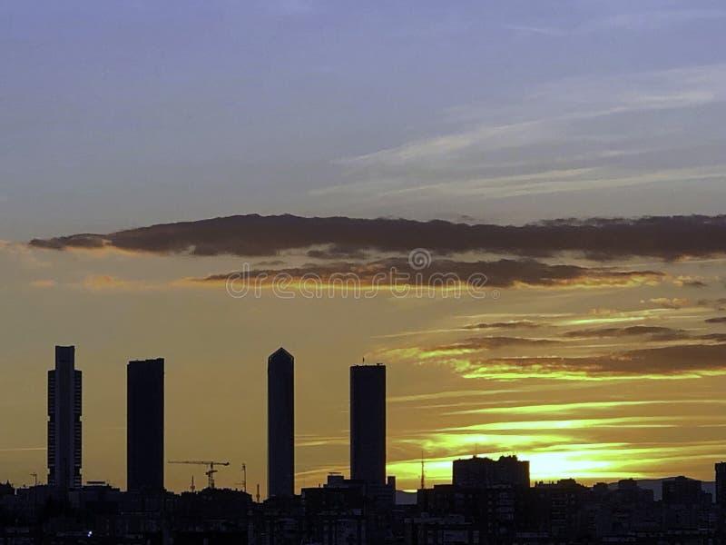 好的日落在有复杂四个的塔的马德里 免版税库存图片