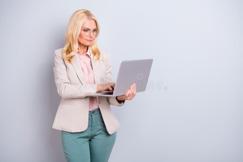 好的有吸引力的时髦的手膝上型计算机Wi-Fi遥控的内容严肃的有波浪头发的夫人顾问藏品画象  免版税库存照片