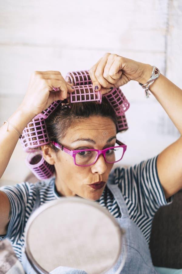 好美丽的人妇女在家有在看什么发生-现代夫人的滑稽的概念的头和镜子的卷发的人的得到的 免版税库存照片