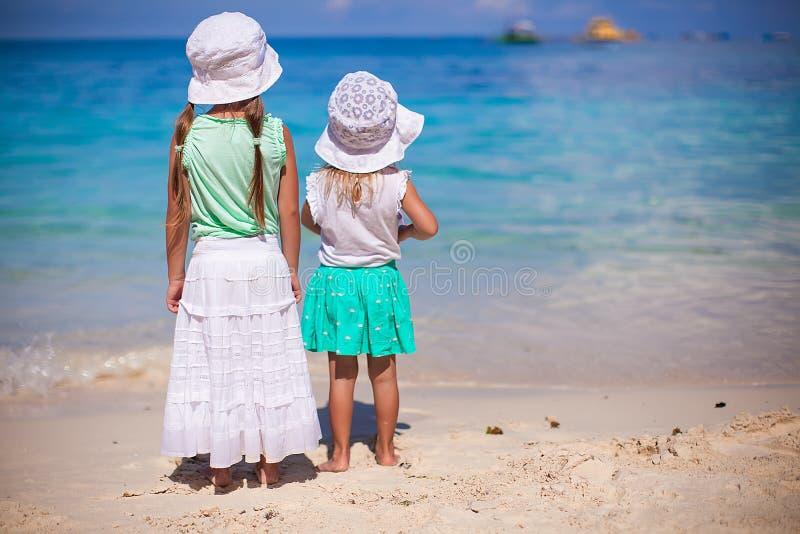 好衣服的小可爱的女孩在白色海滩 免版税库存图片
