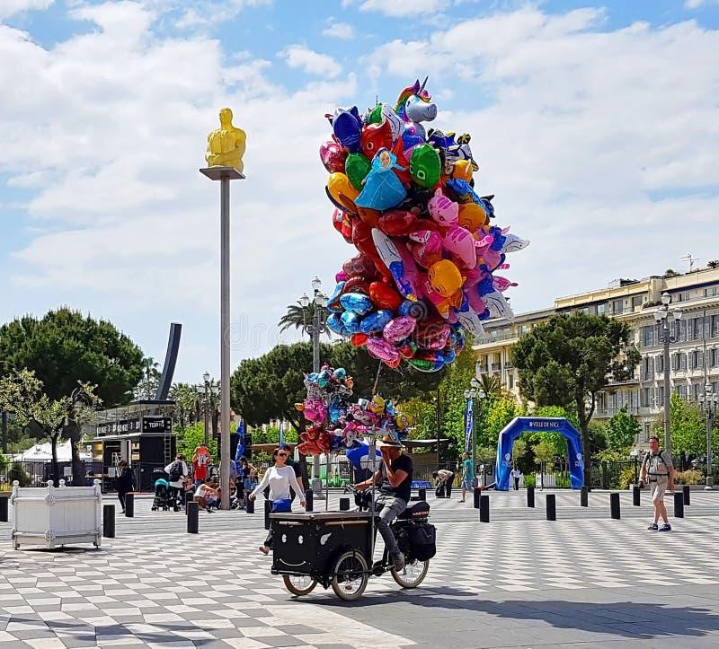 好,法国- 2018年5月:走在地方Massena的纪念品卖主和游人在尼斯,法国海滨,彻特d ` Azur,法国 免版税库存照片