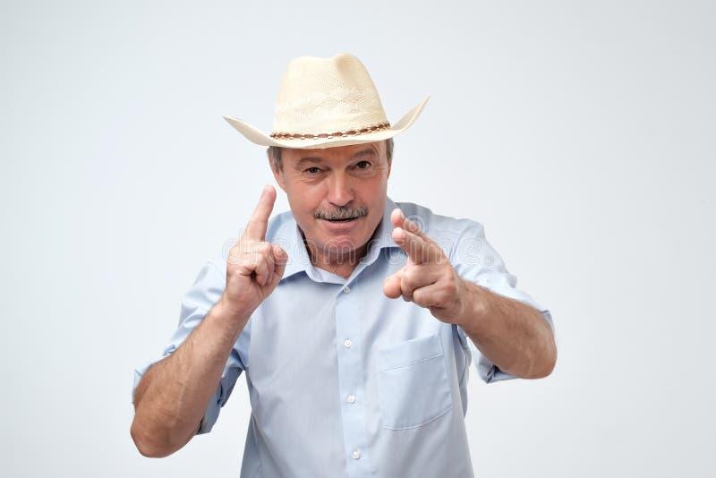 如他向前,射击成熟做与手指的牛仔帽的白种人人一个标志 免版税库存照片