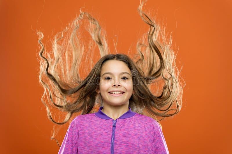 如何对待卷发 好和整洁的发型 做孩子的容易的技巧发型 小儿童长发 迷住 免版税库存图片