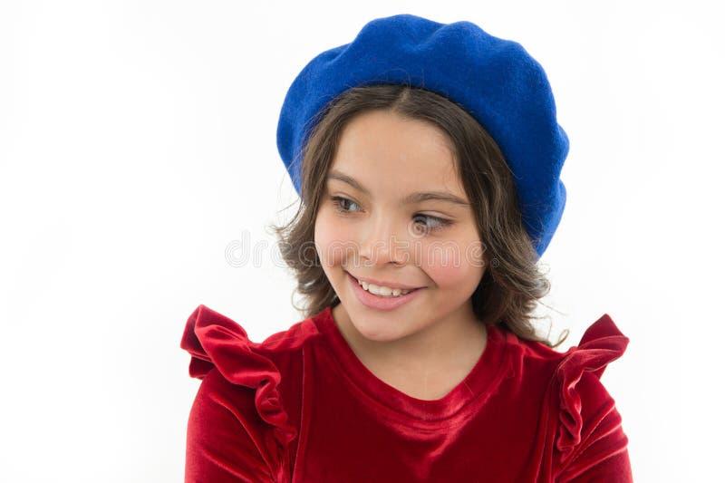 如何穿象时尚女孩的贝雷帽 摆在帽子的孩子一点逗人喜爱的女孩笑容隔绝在白色 时兴 图库摄影