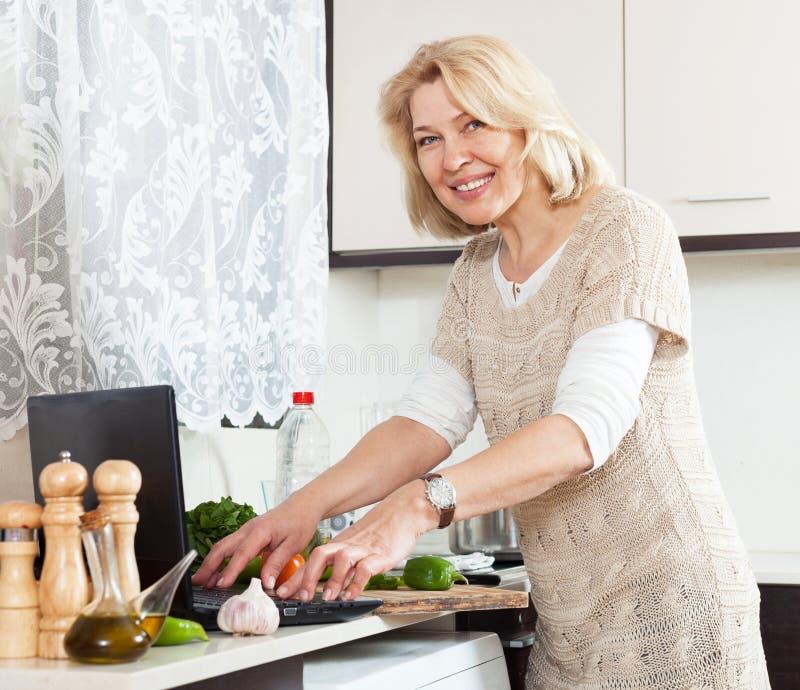 主妇使用烹调汤的笔记本在家的厨房里 免版税库存图片