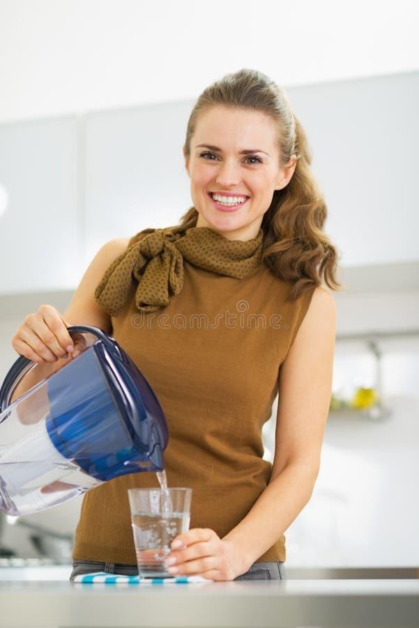 主妇倾吐的水到从滤水器投手的玻璃里 库存图片