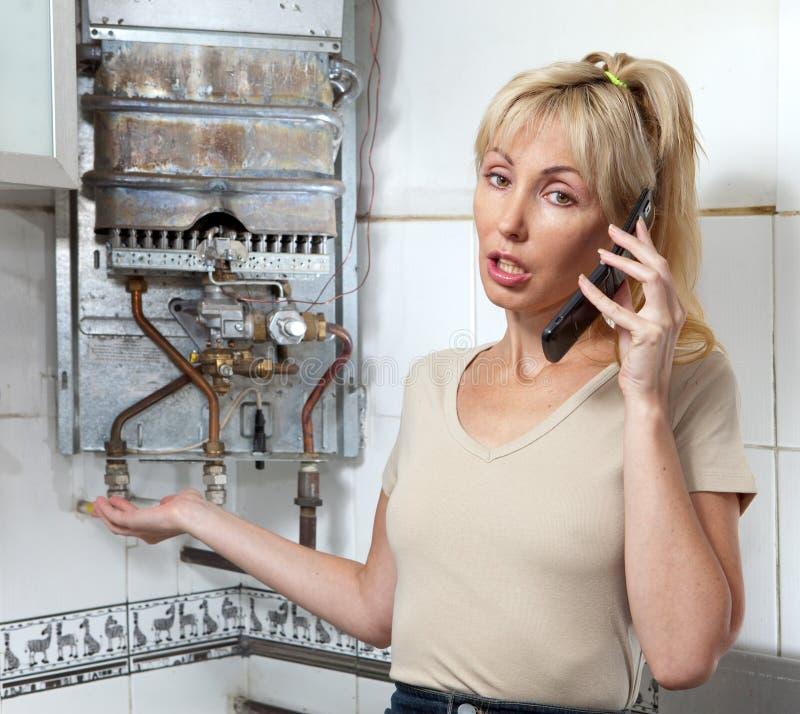 主妇在关于气体水加热器修理的一个车间叫  免版税库存图片