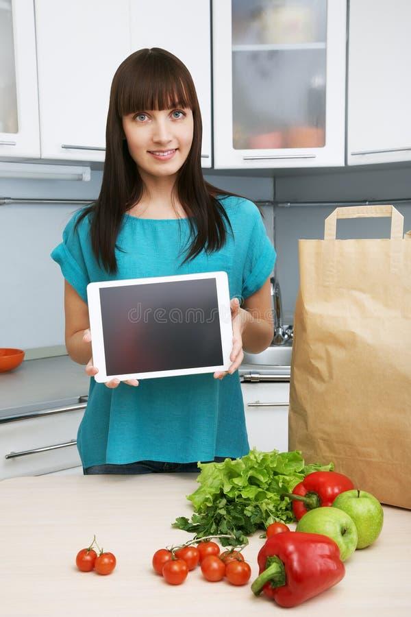 主妇在厨房使用一台片剂计算机 免版税图库摄影