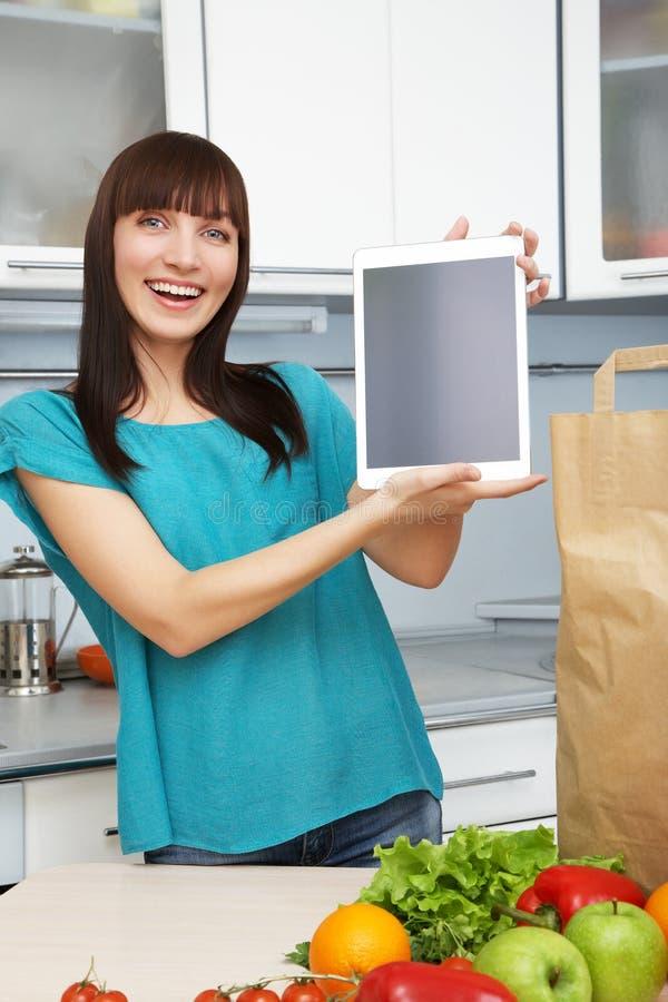 主妇在厨房使用一台片剂计算机 免版税库存图片