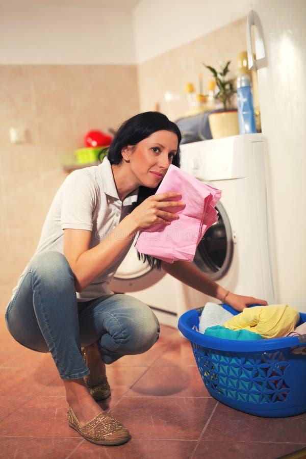 主妇在家做着与洗衣机的洗衣店 免版税库存图片