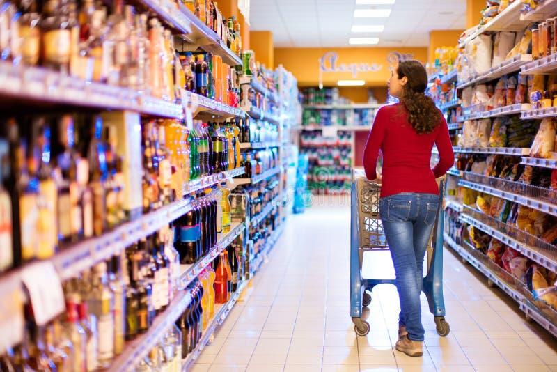 主妇在有空的推车的超级市场 库存照片