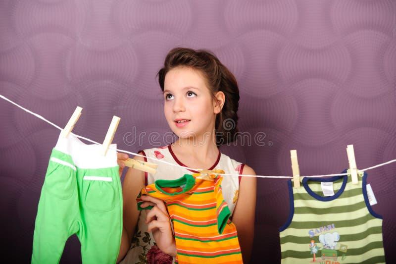 年轻主妇垂悬的衣裳 免版税库存照片