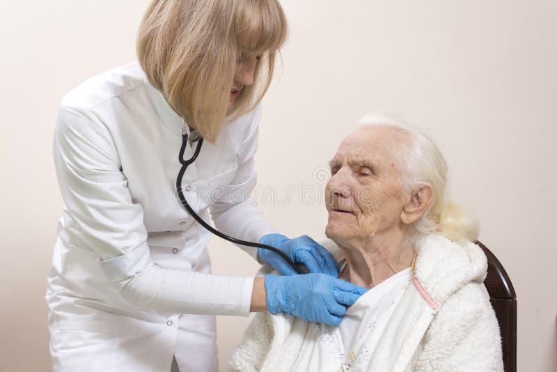 妇女一副白色实验室外套和医疗手套的内科医生医生审查一名非常老灰色妇女的肺有听诊器的 免版税库存图片