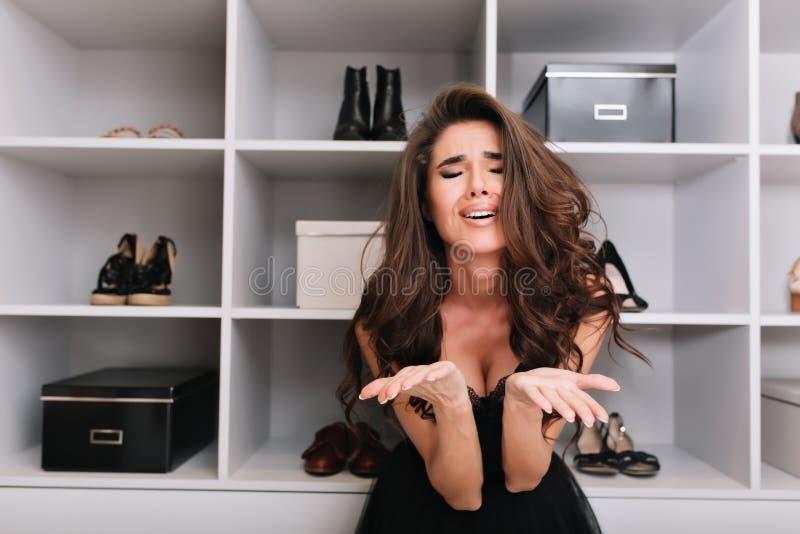 妇女不相当知道怎样佩带,艰苦做出选择,站立在化装室 她看非常生气和 免版税库存照片