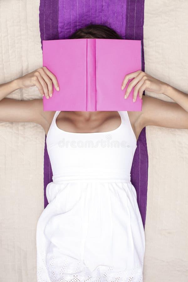 妇女与书的覆盖物面孔,当说谎在野餐毯子时 免版税库存照片