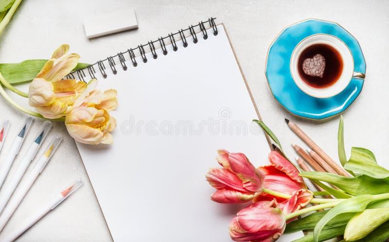 妇女与俏丽的郁金香的春天工作区、笔记本或者写生簿、五颜六色的刷子标志和咖啡杯 免版税库存照片