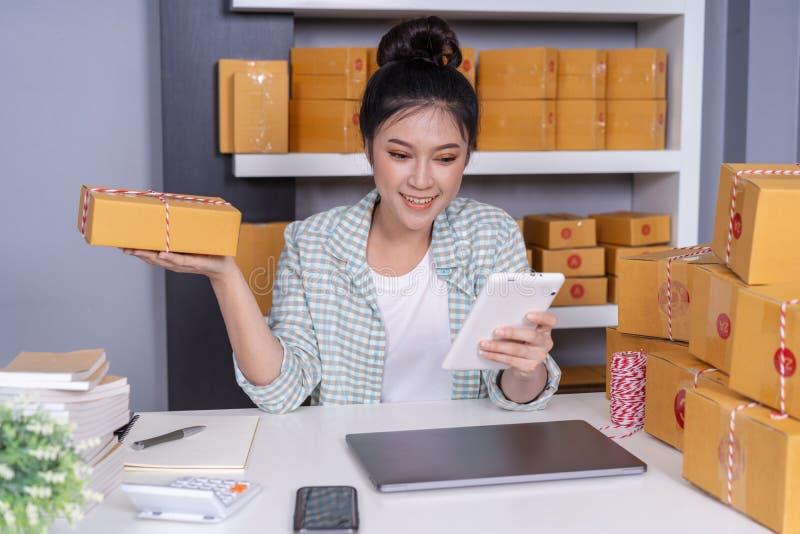 妇女与她的数字片剂和传讯者小包箱子一起使用在 库存图片