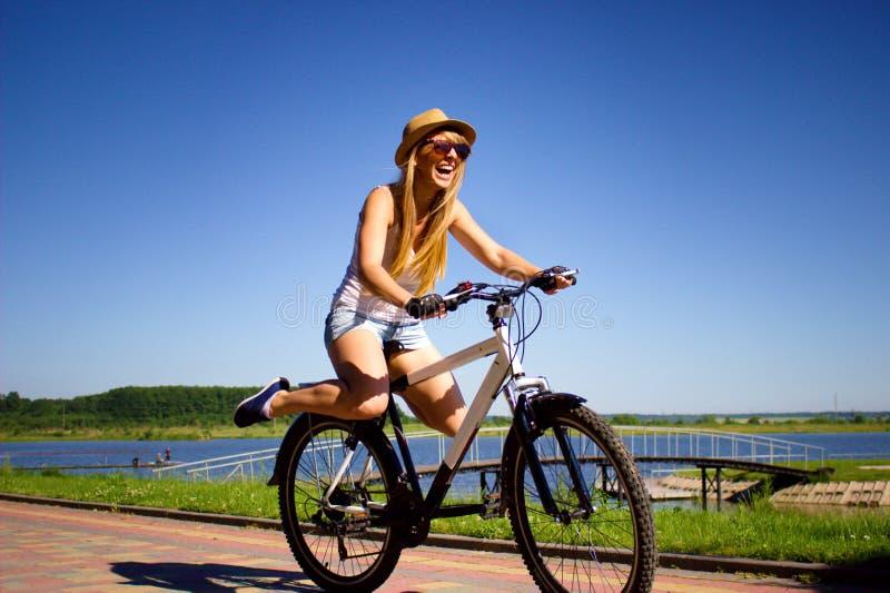 妇女与她的行程的骑马自行车在天空中 图库摄影