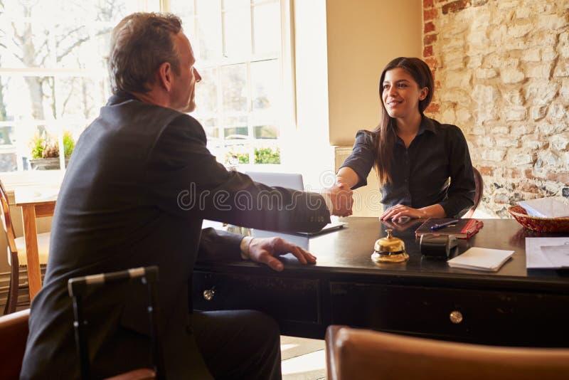 妇女与客人握手在旅馆的报道登记柜台 图库摄影