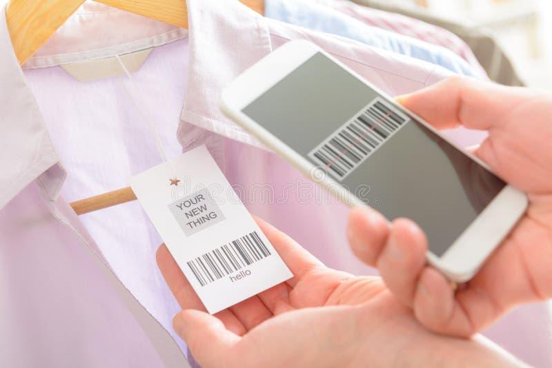 妇女与手机的扫描条形码 免版税库存图片