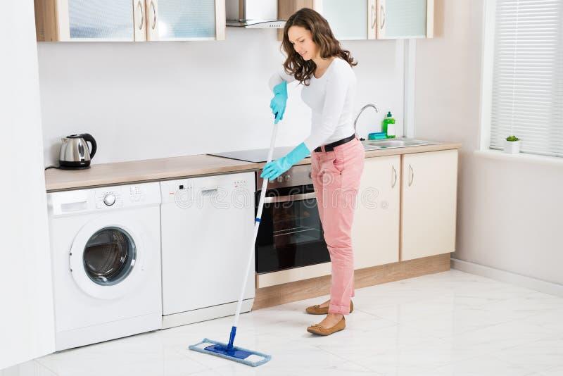 妇女与拖把的清洁地板 库存照片