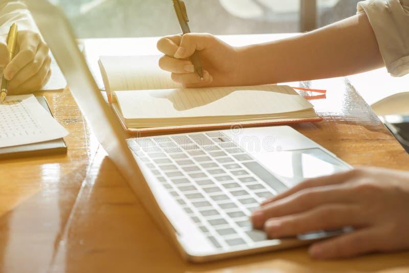 妇女与新的起始的项目一起使用在木头的现代办公室 库存照片