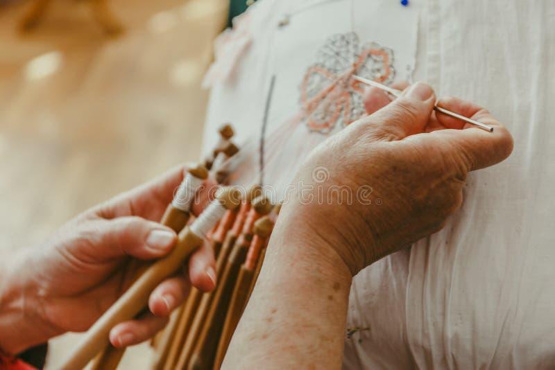妇女与梭结花边的手工特写镜头,手工制造制作系带 库存照片