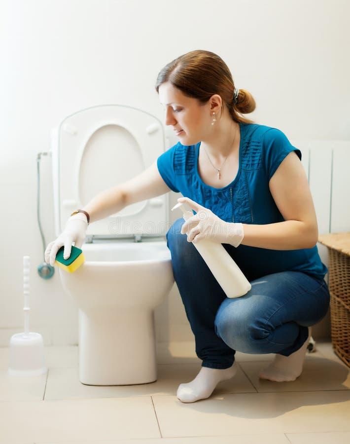 妇女与海绵和擦净剂的清洁洗手间 免版税库存图片