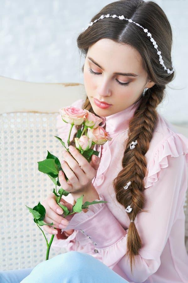 妇女与玫瑰色花的秀丽画象 库存照片