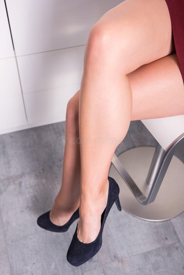 妇女与盘的腿坐一把椅子在办公室 库存照片