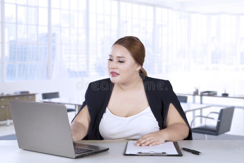 妇女与膝上型计算机和剪贴板一起使用 库存图片
