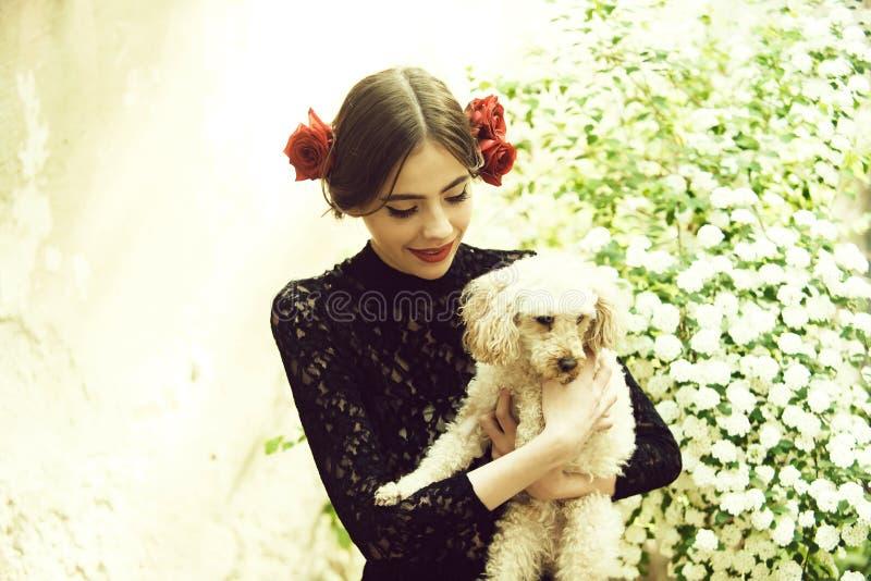妇女与西班牙构成的举行狗,在头发上升了 免版税图库摄影