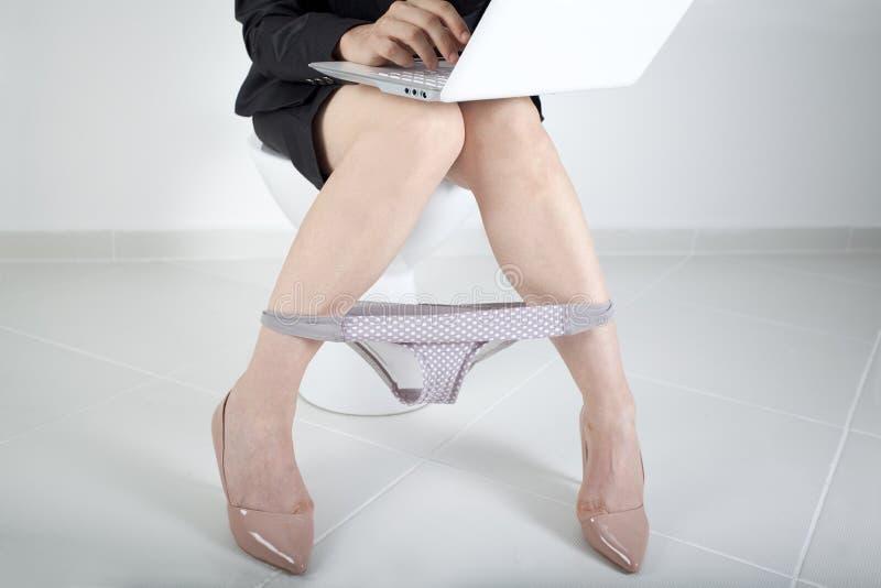 妇女与计算机一起使用在卫生间里 免版税库存照片
