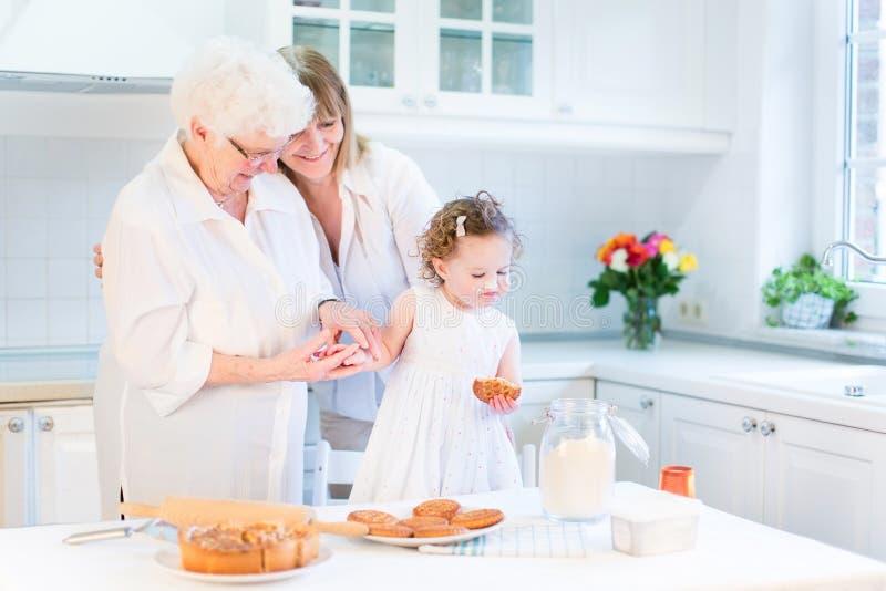 妇女与资深母亲,盛大女儿的烘烤蛋糕 免版税库存图片