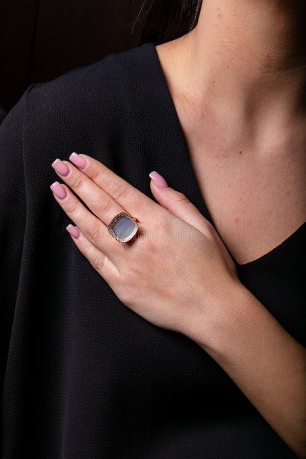 妇女与金刚石边缘的金戒指,与石头在中部在手指,在黑背景 免版税库存图片
