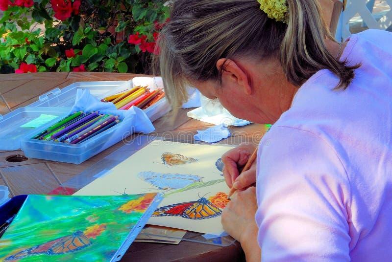 妇女与颜色铅笔的艺术家绘画 免版税库存照片