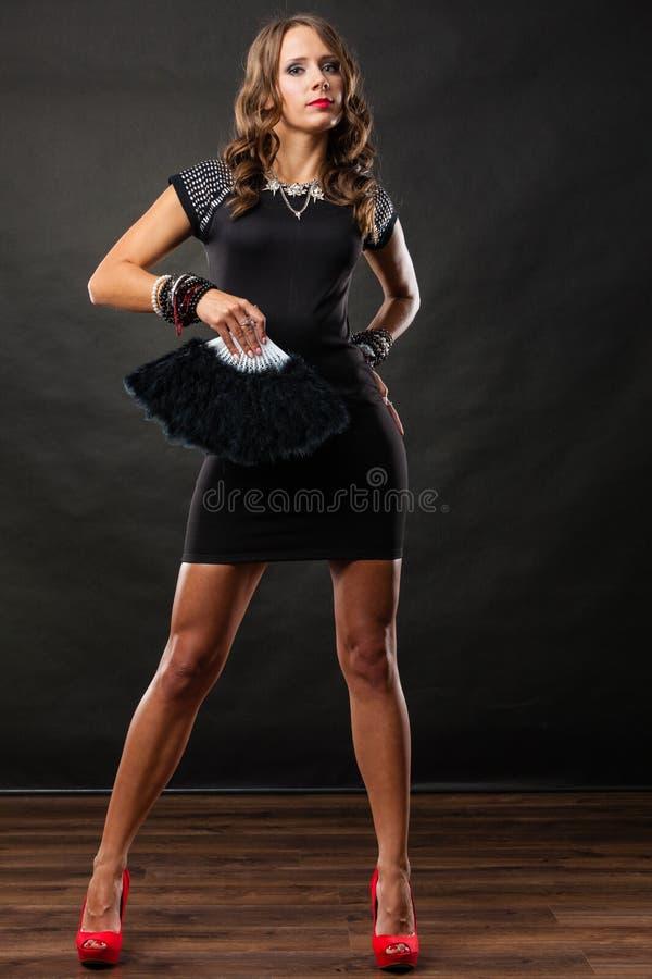 妇女与黑爱好者的晚礼服在手中 免版税库存图片