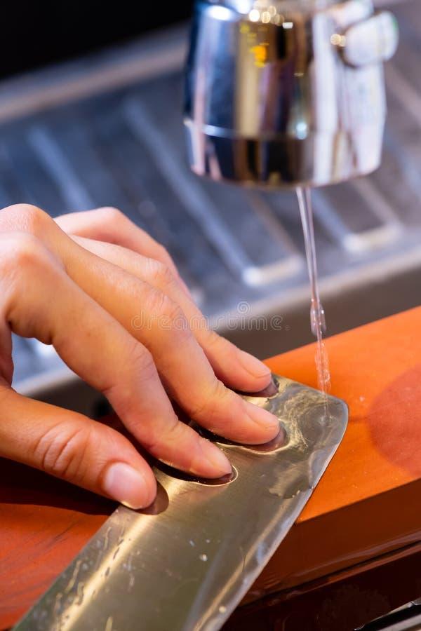 妇女专业厨师手拿着磨的刀子在磨刀石 从日本的优质专业石头 提高过程的刀子 免版税库存照片
