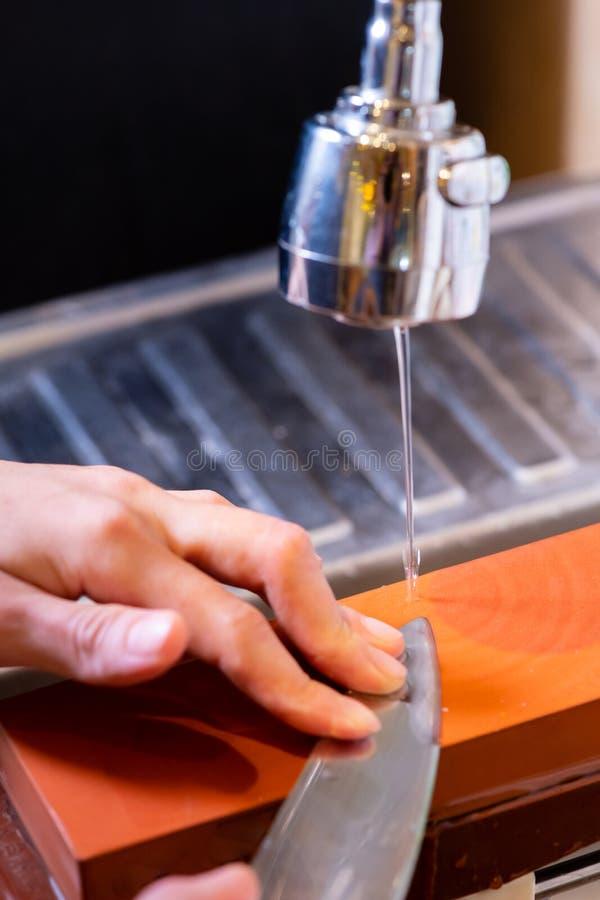 妇女专业厨师手拿着磨的刀子在磨刀石 从日本的优质专业石头 提高过程的刀子 库存照片