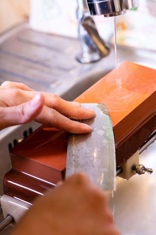 妇女专业厨师手拿着磨的刀子在磨刀石 从日本的优质专业石头 提高过程的刀子 图库摄影