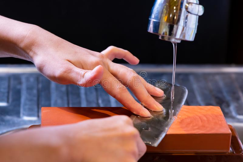 妇女专业厨师手拿着磨的刀子在磨刀石 从日本的优质专业石头 提高过程的刀子 免版税库存图片