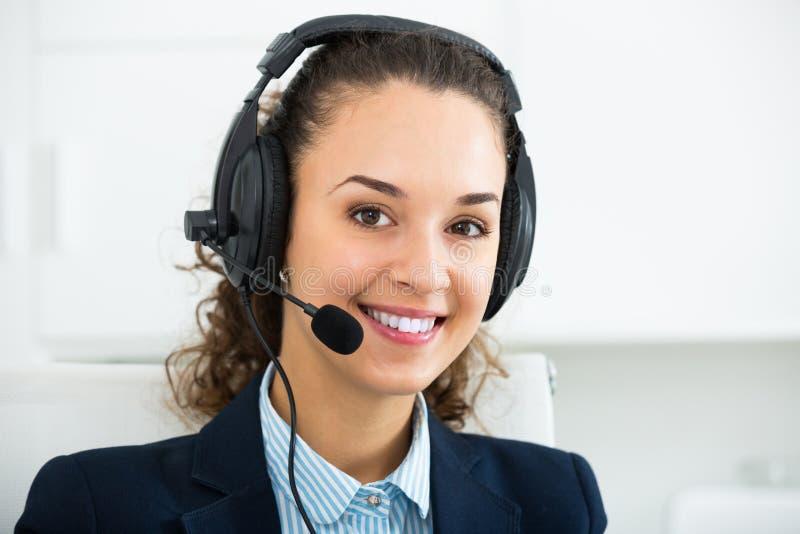 妇女专业电话中心操作员谈话与客户 免版税图库摄影