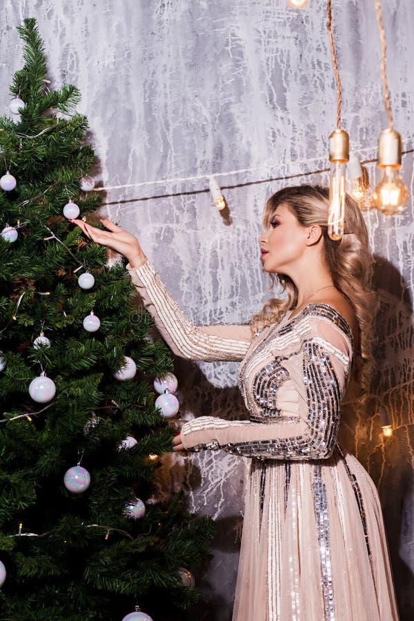 妇女为假日装饰一棵圣诞树 轻的背景 免版税库存照片